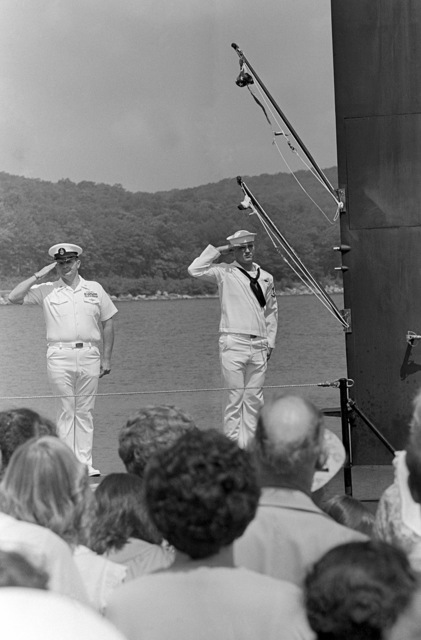 Crew members salute during the commissioning of the nuclear-powered attack submarine USS DALLAS (SSN 700). The commissioning pennant is flying from the mast
