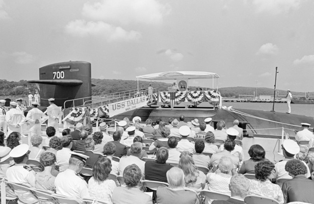 Guests listen to a naval officer speak during the commissioning of the nuclear-powered attack submarine USS DALLAS (SSN 700)