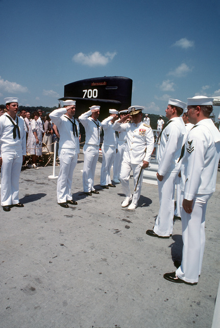 Rear Admiral H.L. (RADM) Young, supervisor of shipbuilding, conversion and repair, exchanges salutes with side boys at the conclusion of the commissioning of the nuclear-powered attack submarine USS DALLAS (SSN 700)