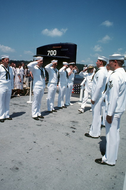 Rear Admiral (RADM) H.L. Young, supervisor of shipbuilding, conversion and repair, exchanges salutes with side boys at the conclusion of the commissioning of the nuclear-powered attack submarine USS DALLAS (SSN 700)