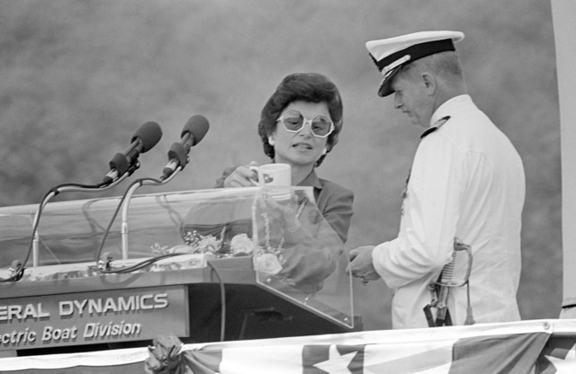 Rita C. Clements, sponsor, presents a gift to Captain (CAPT) Donald R. Ferrier, prospective commanding officer, during the commissioning of the nuclear-powered attack submarine USS DALLAS (SSN 700)