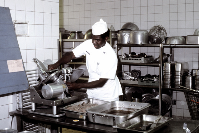 SSGT Walter McCord slices meat in preparation for the evening meal in Eifel Dining Hall
