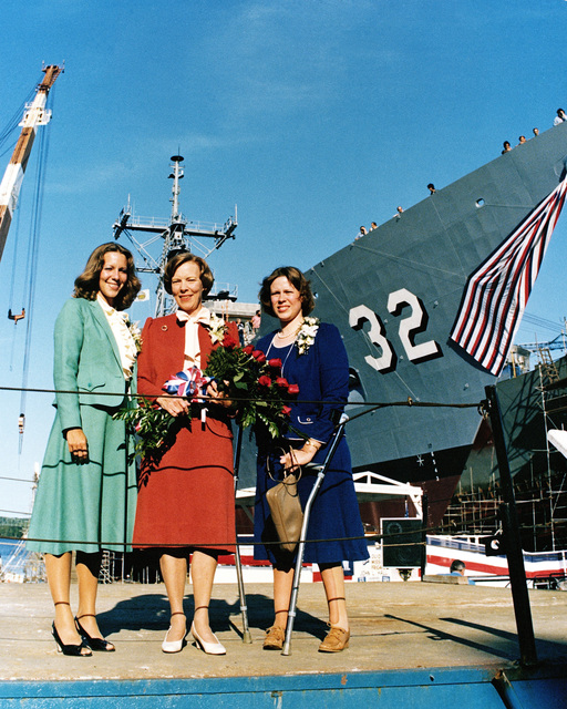 Ann Tyler Godson, maid of honor, left; Dr. Susan Hall Godson, sponsor, center; and Ellen Godson Wood, maid of honor, stand on the speakers platform prior to the launching ceremony for the Oliver Hazard Perry class guided missile frigate USS JOHN L. HALL (FFG 32), background