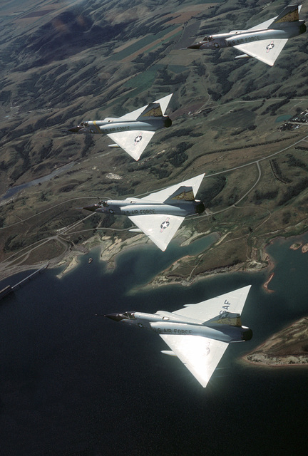 An air-to-air left side view of four-ship wedge formation of F-106 Delta Dart aircraft over the prairie during a training flight. The aircraft are from the 5th Fighter Interceptor Squadron