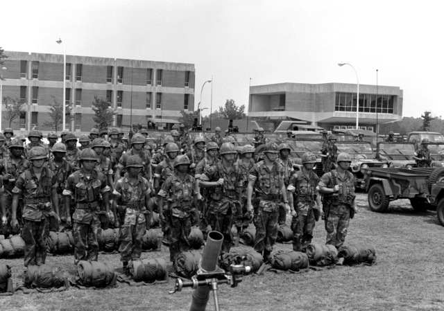 Combat-ready Marines of Weapons Platoon, 8th Marine Regiment, stand at attention for an inspection by Secretary of Defense Caspar W. Weinberger