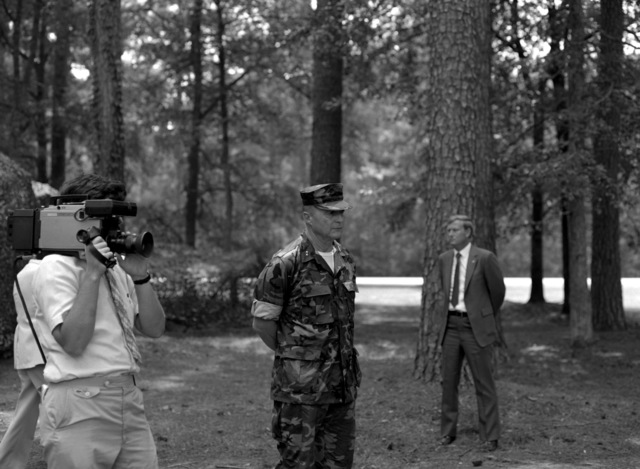 MGEN Charles G. Cooper, commanding general, Marine Corps base, speaks to the officers and men of the 8th Marine Regiment during the visit of Secretary of Defense Caspar W. Weinberger. Standing to the sides of the general are a civilian television cameraman and a secret service agent for Weinberger
