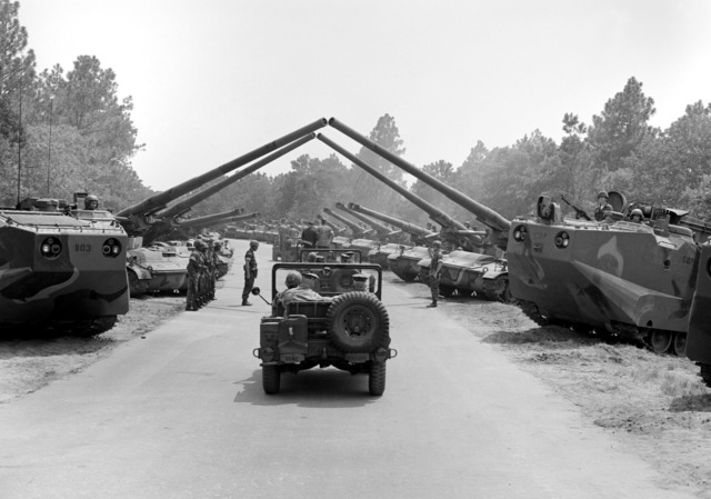 Secretary of Defense Caspar W. Weinberger is taken by jeep to inspect the LVTP-7 command tracked landing vehicle, self-propelled howitzers and M-60A1 tanks. This heavy equipment is staged on both sides of the roadway