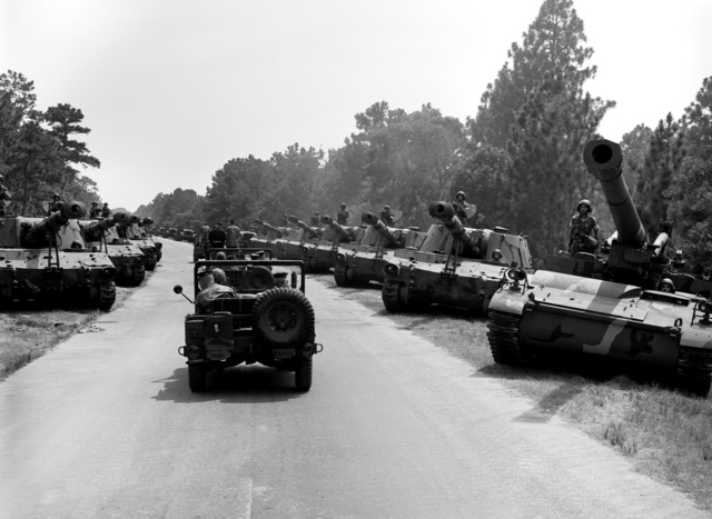 Secretary of Defense Caspar W. Weinberger is taken by jeep to tour the Tank Battalion. M-109 self-propelled howitzers are staged on both sides of the road