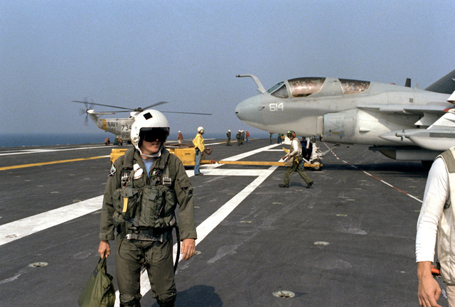 Secretary of the Navy John F. Lehman Jr., in his reserve uniform, walks across the deck upon his arrival aboard the nuclear-powered aircraft carrier USS NIMITZ (CVN-68). The secretary flew to the carrier aboard a Medium Attack Squadron 42 (VA-42) EA-6B prowler aircraft