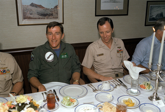 Secretary of the Navy John F. Lehman Jr., left, in his reserve uniform, joins CDR Paul Parcells for a meal aboard the nuclear-powered aircraft carrier USS NIMITZ (CVN-68). Lehman flew out of Naval Air Station, Oceana, Va., with Medium Attack Squadron 42 (VA-42) aboard an A-6 Intruder aircraft