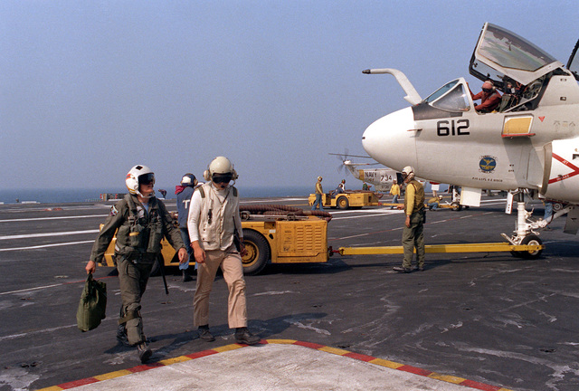 Secretary of the Navy John F. Lehman Jr., left, is escorted across the flight deck by a crewman upon his arrival aboard the nuclear-powered aircraft carrier USS NIMITZ (CVN-68) for a visit. In the background an EA-6B Prowler aircraft is maneuvered into a parking area