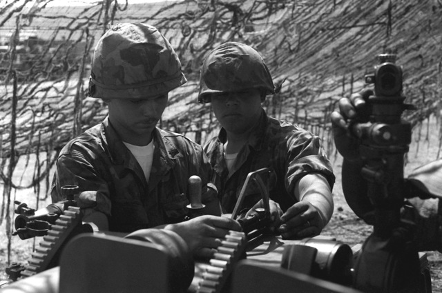 Two Marine 105mm howitzer gun crewmen, from Btry. I, 3rd Bn., 11th Marines, prepare their gun for a fire mission