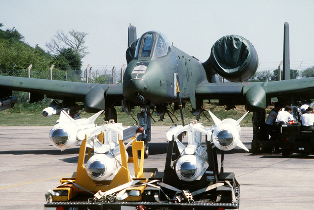 A front view of an A-10 Thunderbolt II aircraft being uploaded with AGM-65 Maverick missiles