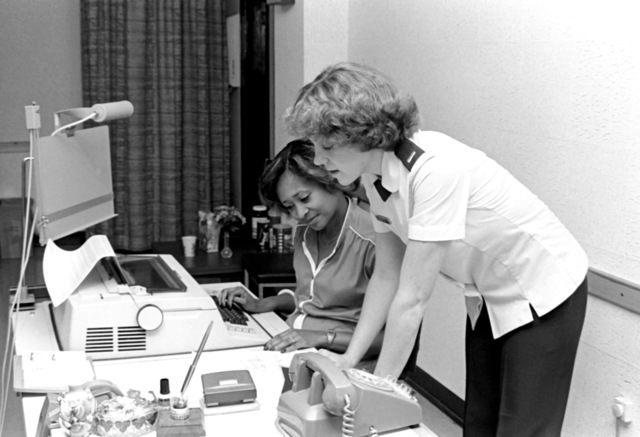 LT. Barbara Warner, right, 7350th Air Base Group, Tempelhof Central Airport, explains a work order to Marcella Garrett, a word processor operator