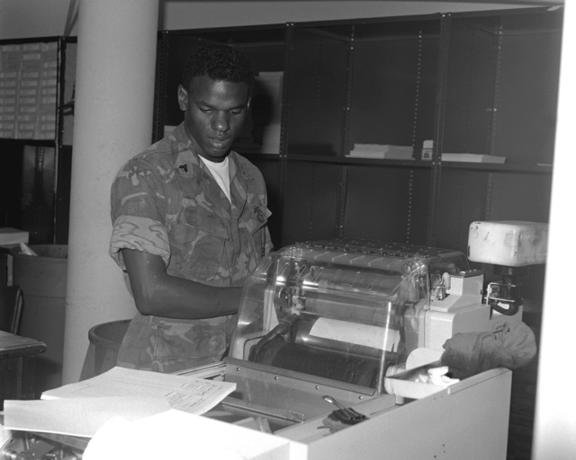 CPL Victor Branch checks the alignment of the Multilith 1250 offset press as the copy material comes off the machine. This piece of equipment is in the Reproduction Section of the Graphic Arts Branch of the Facilities and Services Division at the Marine Corps Logistics Base