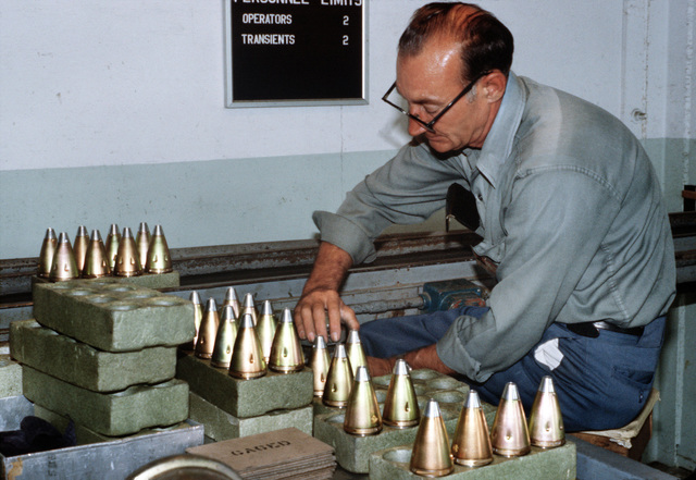 A civilian worker gages standard contour 557 artillery fuses at the Seneca Army Depot