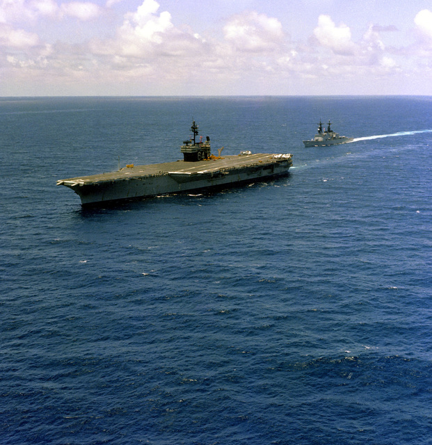 A port bow view of the aircraft carrier USS CONSTELLATION (CV-64) and the destroyer USS FIFE (DD-991) underway off the coast of California