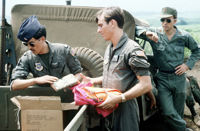 LT Robert Reneau, left, and LT Dove Loar from the 345th Tactical Airlift Squadron unload target cloths while MAJ Carl Dommeyer from the 316th Tactical Airlift Group looks on