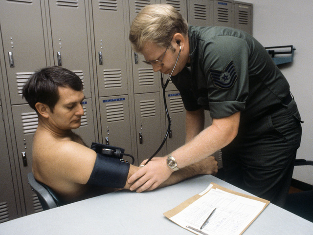 Flight operations supervisor TSGT Bruce L. Lohse checks blood pressure of MAJ Barry C. MacKean