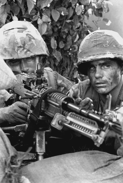 """Private First Class J. Graham, a machine gunner with Company F, 2nd Battalion, 4th Marines aims his M-60 machine gun from a foxhole as his """"A"""" gunner, PFC J. Pilar, feeds the bullets. They are part of Battalion Landing Team 2/4 participating in the Marine Corps Combat Readiness Evaluation System (MCCRES) test at Camp Schwab"""