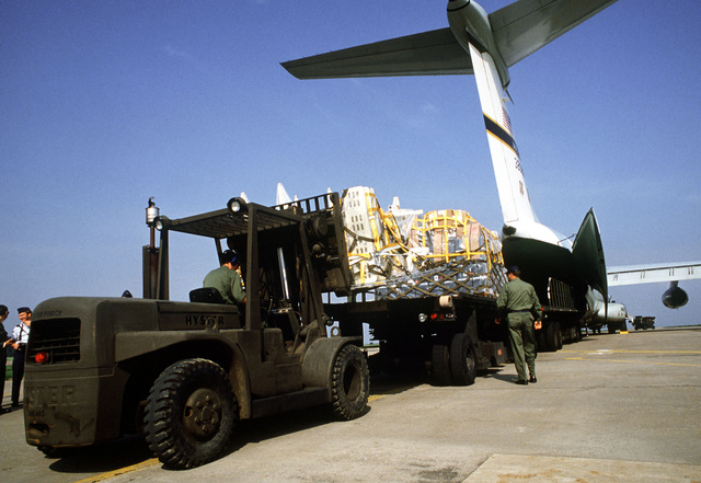 A heavy duty forklift and K-loader are used by the 50th Component Repair Squadron, to unload F-16 avionics test equipment from this C-141B Starlifter aircraft