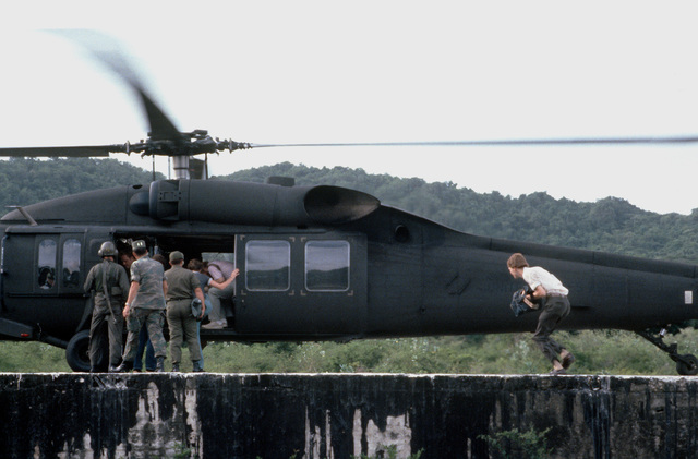 Members of the press prepare to board a UH-60 Blackhawk helicopter for transportation to the drop zone, as preparations are made for the start of Exercise Ocean Venture '81