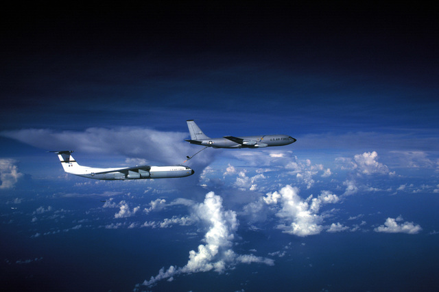 Right side air-to-air view of a KC-135 Stratotanker aircraft (front) refueling a C-141 Starlifter aircraft during Exercise OCEAN VENTURE '81