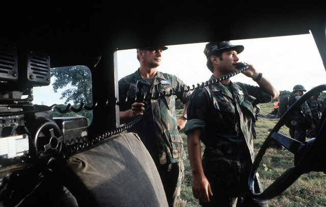 TSGT Richard E. Heins (left), watches as SSGT Dale Watkins talks to the lead C-141 Starlifter aircraft prior to the air drop of two jeeps as Exercise Ocean Venture '81 gets underway