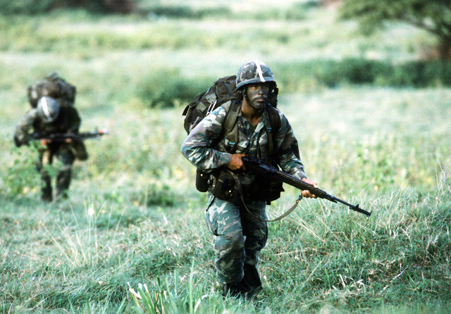 Two Airborne Rangers from the 2nd Battalion, 75th Infantry, armed with M-161A rifles, move out toward a central gathering place after being dropped from a C-141 Starlifter aircraft at the start of Exercise Ocean Venture '81