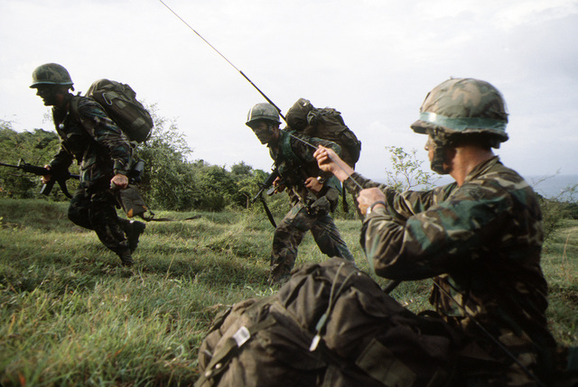 Airborne Rangers from the 2nd Battalion, 75th Infantry, move out toward a central gathering place after they were dropped from a C-141 Starlifter aircraft, at the start of exercise Ocean Venture '81