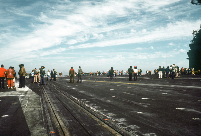 Civilians and crewmen walk along the flight deck of the aircraft carrier USS CORAL SEA (CV-43) during a Dependents' Day Cruise