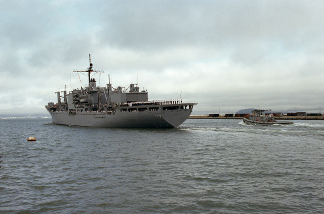 Crew members man the rails of the Mars-class combat store ship USS SAN JOSE (AFS 7) as it leaves Alameda, California, for its new home port in Guam