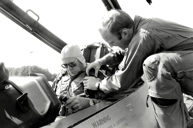 CPT Denny Granquist of the 32nd Tactical Fighter Squadron helps Ambassador to Belgium Charles H. Price with final preparations before his flight in an F-15D Eagle aircraft