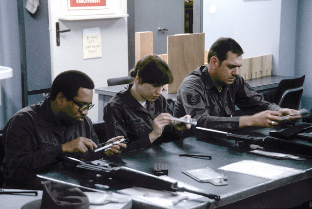 TSGT Ellie J. Robeson, A1C Laura D. Lamond and TSGT Edwin W. Hannam Jr., left to right, learn to dismantle and reassemble the M-16 rifle at Tempelhof Central Airport