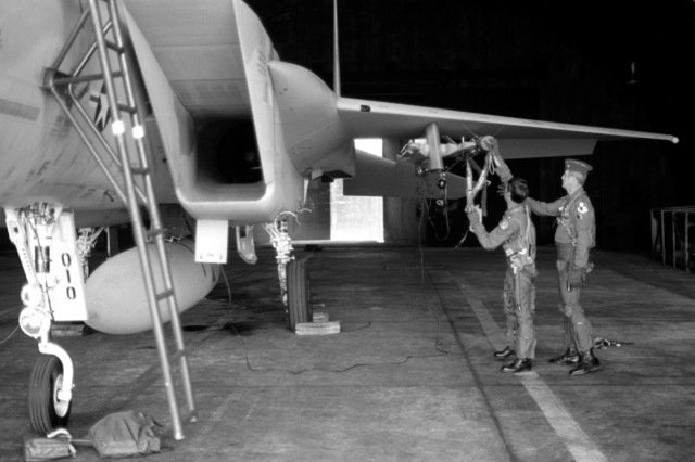 LTC Andrews, left, and COL Chase, commander, 52nd Tactical Fighter Wing, preflight the missiles mounted on an F-15 Eagle aircraft