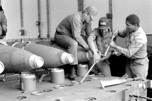 A1C Daniel H. Rousseau, A1C Douglas B. Penman and SRA Cecil A. Haynes Jr., left to right, assemble a laser-guided bomb during a timed build-up exercise