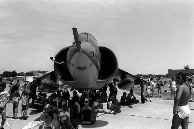 Visitors sit in the shade of an AV-8 Harrier aircraft while attending the Detroit Air Show
