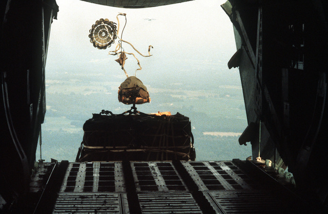 View of a pallet of cargo being airdropped from a C-141B Starlifter aircraft, seen from the inside of the aircraft