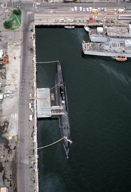A high angle view of the attack submarine USS DARTER (SS-576), the guided missile destroyer USS BERKELEY (DDG-15) and the frigate USS HEPBURN (FF-1055) docked at the pier