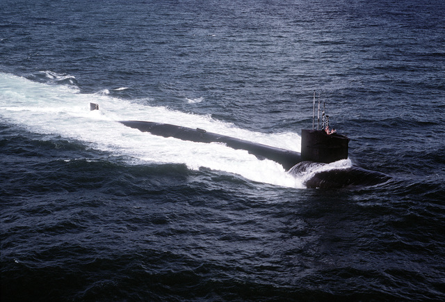 A starboard side view of the nuclear-powered attack submarines USS HADDOCK (SSN-621) underway with crewmen riding the sail