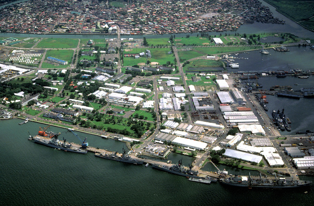 A view of the Naval Base, Subic Bay, with the city of Olongapo in the background. The ships docked at the pier in the foreground are, from right: the oiler USNS HASSAYAMPA (T-AO-145), the guided missile cruiser USS STERETT (CG-31), the guided missile destroyer USS HENRY B. WILSON (DDG-7) and the guided missile cruiser WILLIAM H. STANDLEY (CG-32)