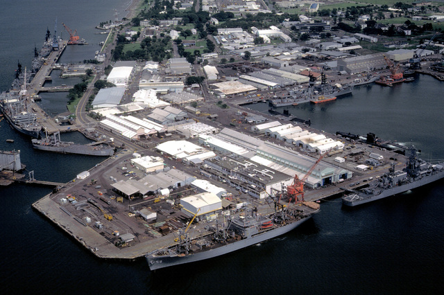 A view of the pier area with docked ships including the auxiliary stores ship USNS RIGEL (T-AF-58) and the nuclear-powered guided missile cruiser USS BAINBRIDGE (CGN-25) in the foreground. At left are the oiler USNS HASSAYAMPA (T-AO-145), the guided missile cruiser USS STERETT (CG-31), the guided missile destroyer USS HENRY B. WILSON (DDG-7) and the guided missile cruiser USS WILLIAM H. STANDLEY (CG-32)