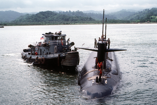 The large harbor tug OPELIKA (YTB-798) pulls up along the starboard side of the nuclear-powered attack submarine USS HADDOCK (SSN-621) before towing the submarine into port