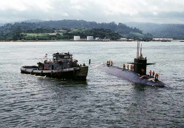 The large harbor tug USS OPELIKA (YTB-798) pulls up along the starboard side of the nuclear-powered attack submarine USS HADDOCK (SSN-621) before towing the submarine into port