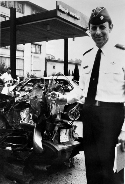LT. COL. Whittenberger stands next to the remains of an automobile destroyed by bombs that also damaged the United States Air Forces in Europe headquarters