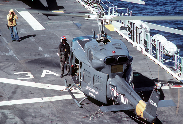 A flight deck crewman aboard the amphibious assault ship USS SAIPAN (LHA-2) prepares a UH-1N Iroquois helicopter for flight. The SAIPAN is taking part in exercise Ocean Venture '81