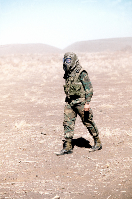 A Marine dressed in camouflage utilities, a flack jacket, and a M-17A1 field protective mask hood, walks across the dusty terrain. He is a part of Kilo Btry., 1ST Bn., 12th Marines. The battalion is going through combat readiness evaluation at the Pakalula Training Area