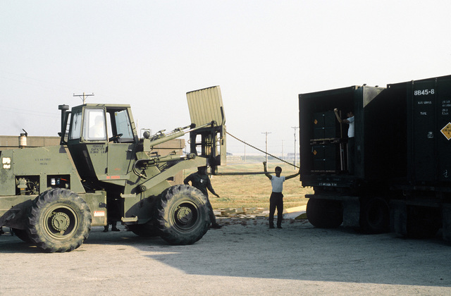 A military van is unloaded from an Army trailer, with the use of a forklift, for reloading onto a flatbed railroad car. The van contains a munitions shipment that arrived at the Chinhae Water Port