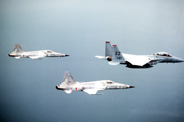A right side view of an F-15A Eagle aircraft from 67th Tactical Fighter Squadron, front, and two F-5 Tiger II aircraft from the Royal Singapore Air force. The aircraft are involved in a joint U.S.-Australian Air Force exercise Pacific Consort