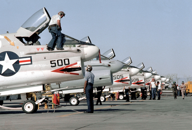 A row of parked Naval Air Reserve Attack Squadron 305 (VA-305) A-7 Corsair II aircraft. Personnel from the unit are performing maintenance on the aircraft during active duty training